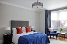 a stylish bedroom with light grey walls brought to life with medium blue curtains, armchair and throw, contrasted with burnt orange cushions on the bed