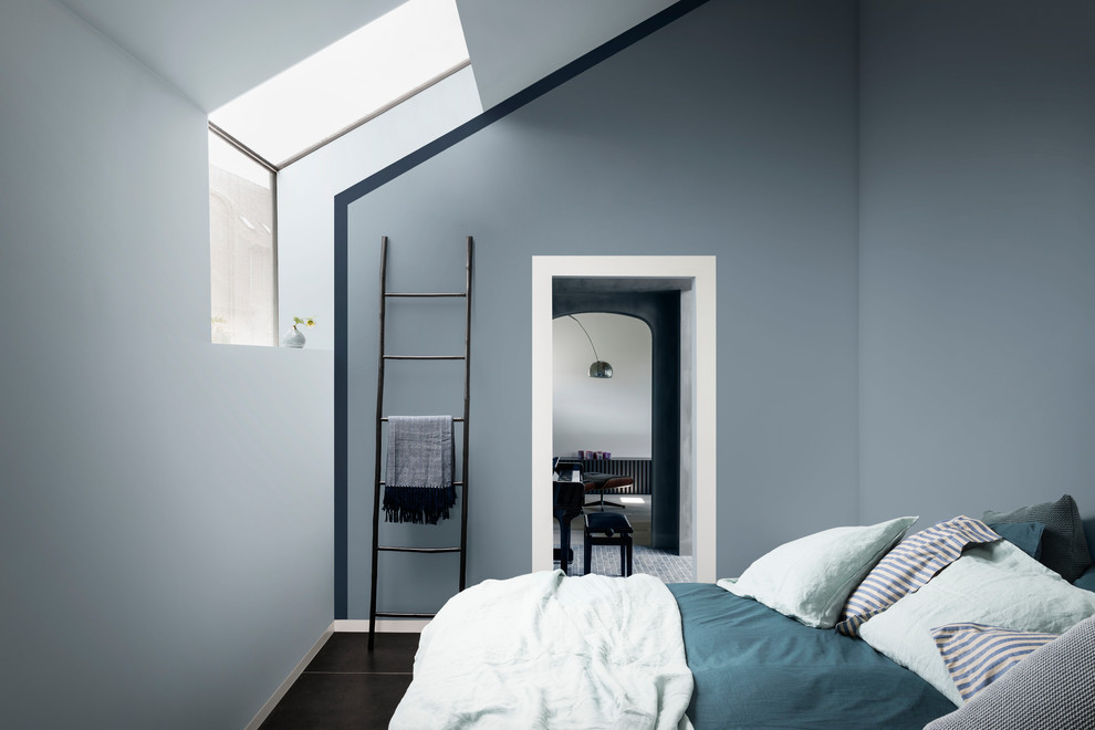 a small and minimalist attic bedroom done in moody blues and with teal and turquoise bedding