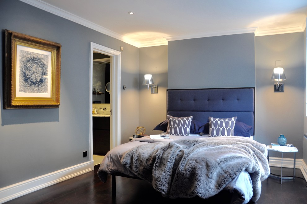 a contemporary bedroom with grey walls and furniture and a stunning upholstered navy bed plus grey pillows and a blanket