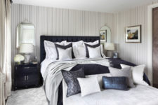 a luxurious vintage-inspired bedroom with pinstripe walls and a stunning navy blue upholstered emperor bed, grey and navy textiles and accessories