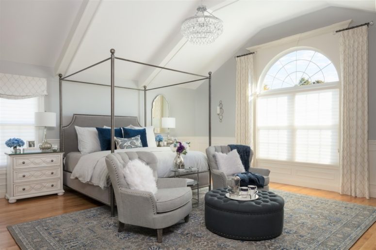 a welcoming bedroom with dove grey furniture and a grey rug plus some navy accents like pillows