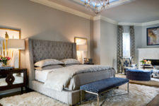 a light grey bedroom with much texture and a single navy accent – an upholstered bench