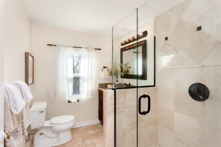 a beige and creamy bathroom with white appliances and touches of black for drama (Seattle Staged to Sell and Design LLC)