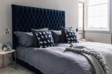 a beautiful bedroom done in dove grey with plenty of texture and a chic teal velvet upholstered bed
