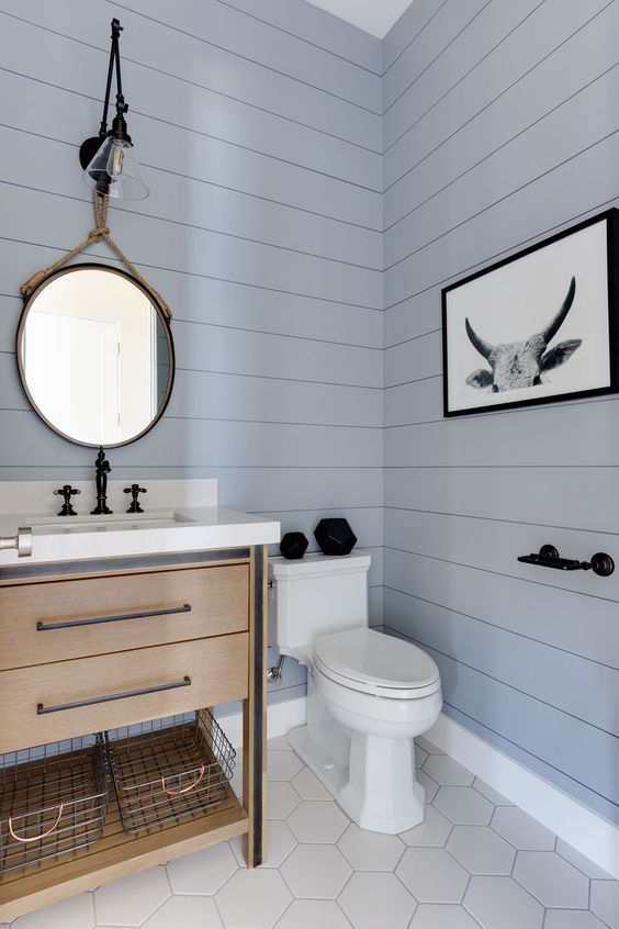 a beautiful contemporary light blue powder room, a wooden vanity, hex tiles on the floor and a mirror hanging on rope