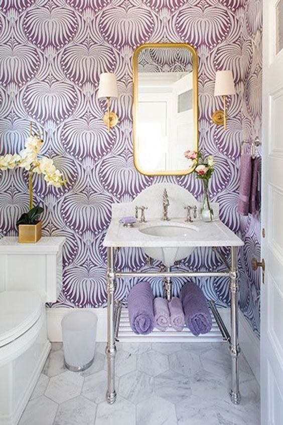 a beautiful purple and white bathroom with printed wallpaper, gilded touches and lamps and an orchid