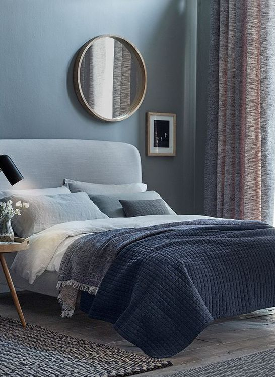 a blue bedroom with light grey floors and a light grey upholstered bed plus grey bedding