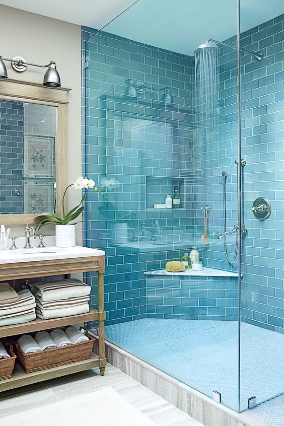 a bold blue tile shower space paired with a grey marbled tile floor and a vintage wooden vanity