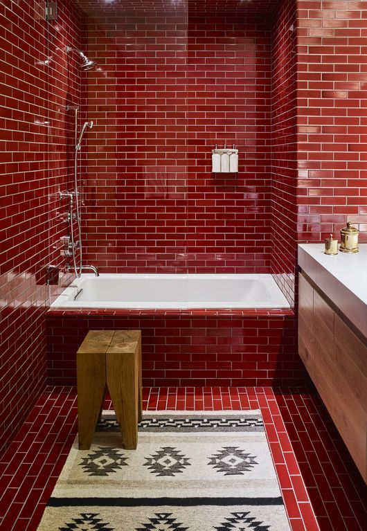 a bold red bathroom fully clad with tiles and accented with white grout plus touches of wood and white