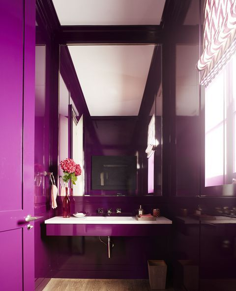 a bright contemporary bathroom done in purple, with an oversized mirror and a floatign sink plus printed shades