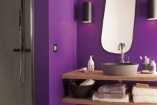 a bright contemporary bathroom with a purple part and a grey shower space, a floatign wooden vanity and a catchy-shaped mirror