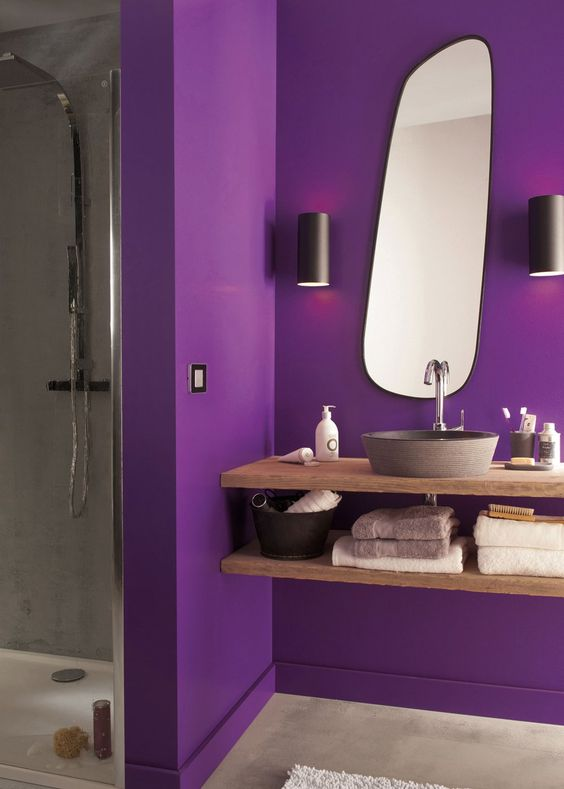a bright contemporary bathroom with a purple part and a grey shower space, a floatign wooden vanity and a catchy shaped mirror