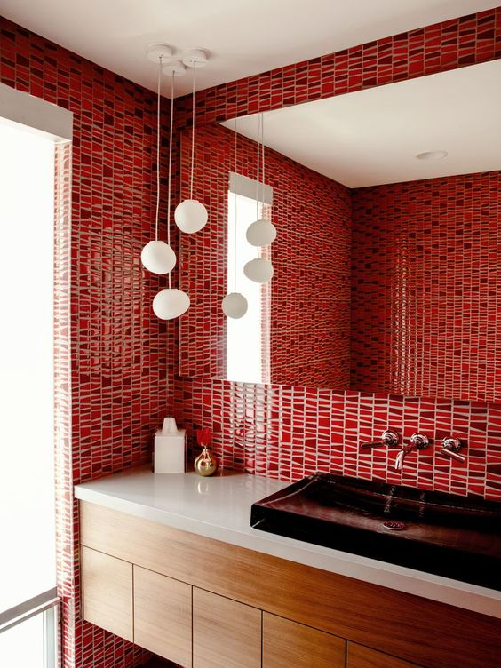 a bright red bathroom clad with bold mosaic tiles, a dark sink and pendant lamps