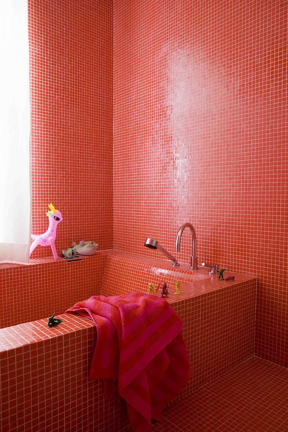 a bright red bathroom fully clad with tiles including the bathtub is a bold idea for a kid