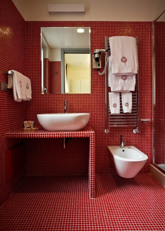 a bright red bathroom fully clad with tiles including the shower space and vanity, with white appliances and white towels