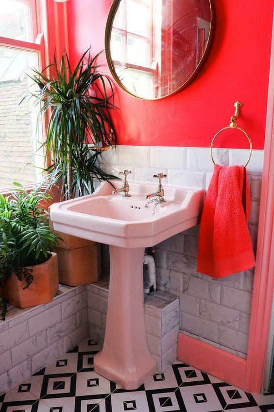 a bright red bathroom with white marble tiles, a white sink, mosaic tiles on the floor and potted plants to refresh the space