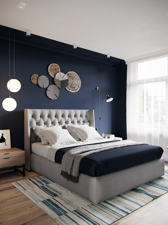 a chic bedroom with a navy statement wall, a grey upholstered bed, some catchy lights and lamps
