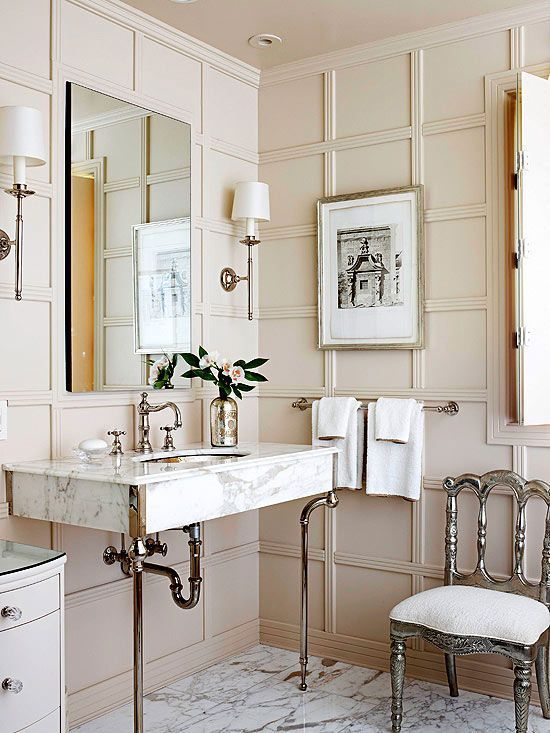 a chic beige bathroom done with wall panels, elegant furniture and lamps and a marble sink on tall legs
