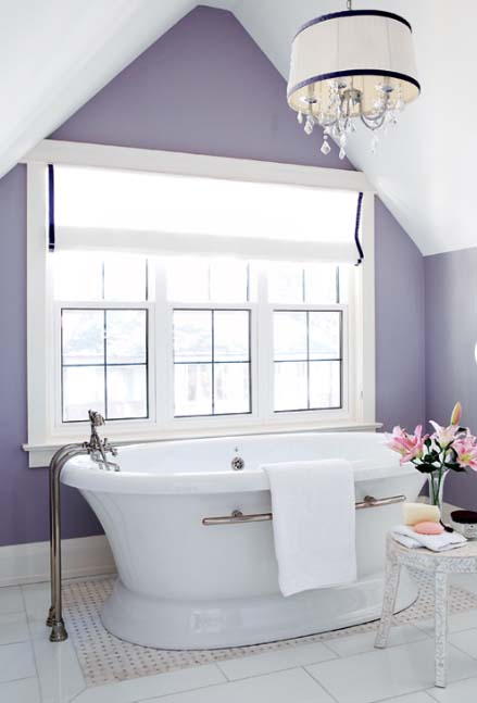 a chic vintage inspired bathroom with purple walls, a gorgeous comfy bathtub and an elegant chandelier