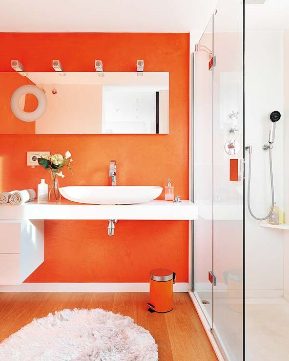 a contemporary bathroom with an orange statement wall, a matching trash can and some hardware plus refreshing whites
