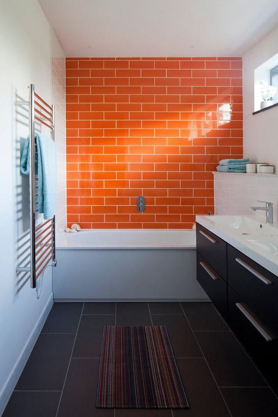 a contrasting grey and white bathroom is accented with a dark stained floating vanity and a bright orange tile wall