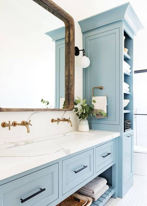 a cozy rustic bathroom with light blue furniture, a wooden frame mirror and brass fixtures