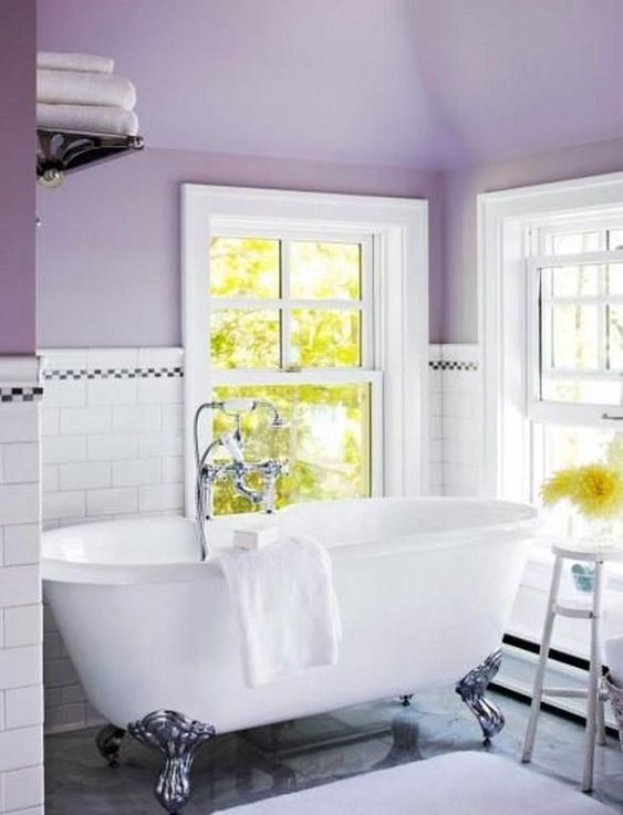 a cozy vintage-inspired bathroom with purple walls and white subway tiles plus a chic clawfoot bathtub