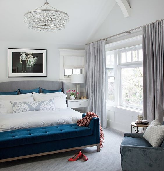 a dove grey and creamy bedroom with a navy bench, pillows and a blue chair