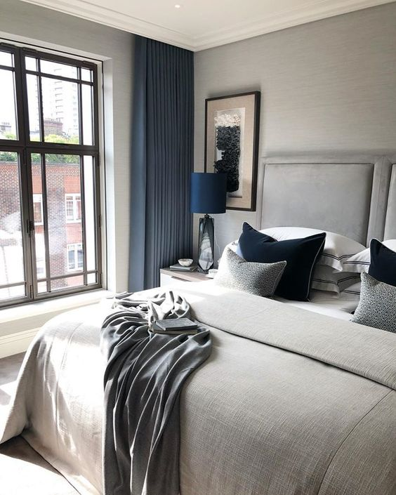 a dove grey bedroom with bold blue touches shows off luxury and beauty