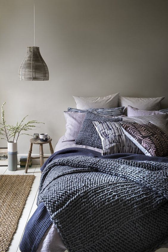 a dove grey bedroom with layered navy blue and blue bedding and a wicker lampshade