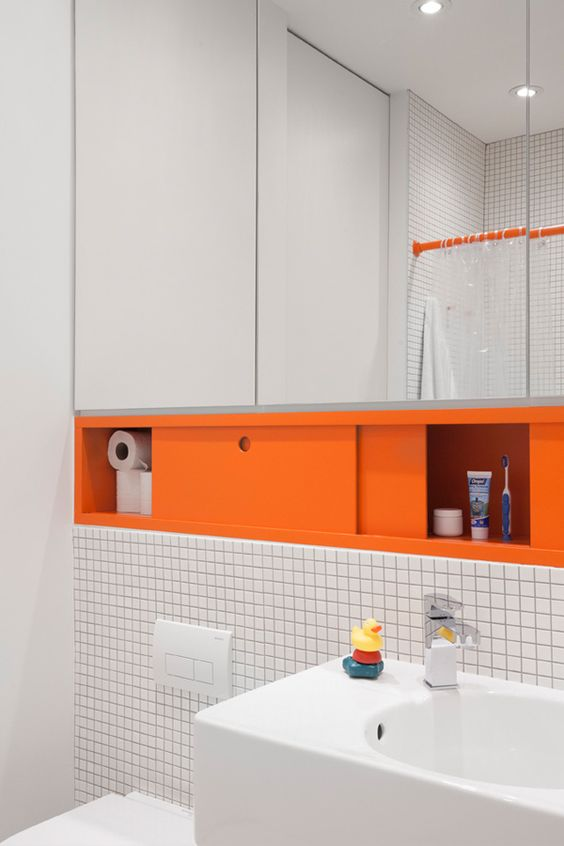 a floating mirror with a storage compartment done in orange is a non-typical way to add color to your space