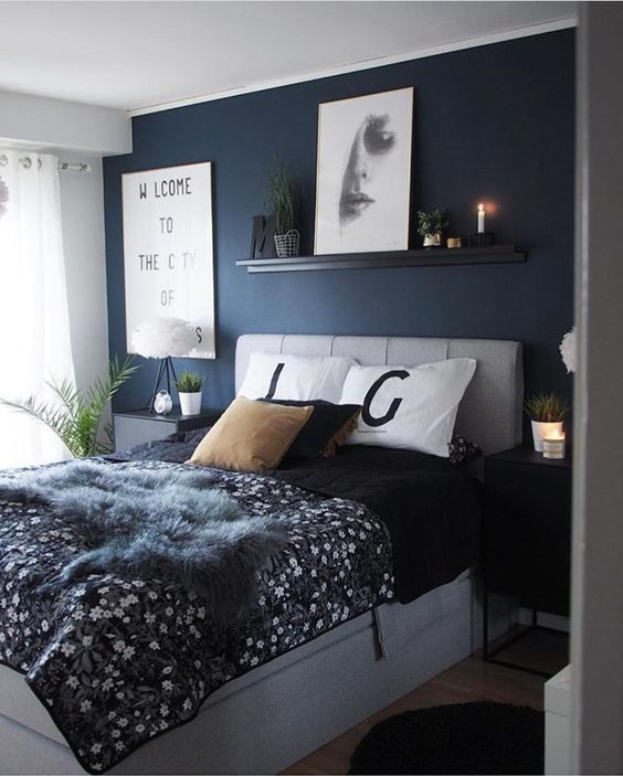 a grey and navy bedroom with a statement wall, a grey upholstered bed and nightstands, some modern artworks