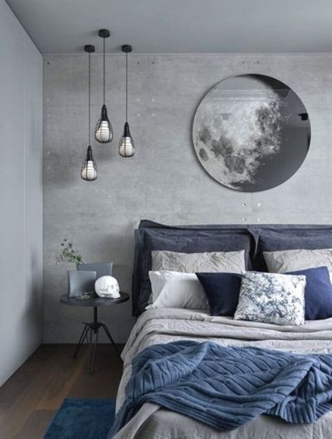 a grey bedroom with a concrete statement wall, an upholstered bed and touches of navy blue