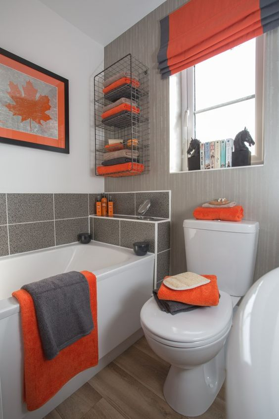 a grey, orange and white bathroom with all the colors mixed up stylishly and some catchy decor elements here and there