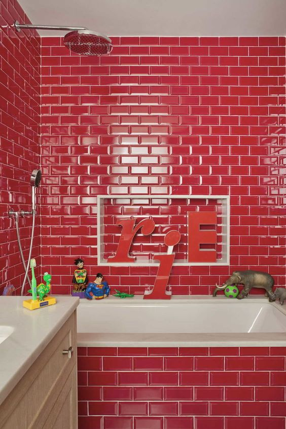 a hot red bathroom clad with tiles and accented with white grout, a neutral vanity and a white sink