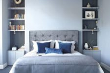 a light blue bedroom with grey niches, a grey upholstered bed and floor plus bold blue accents