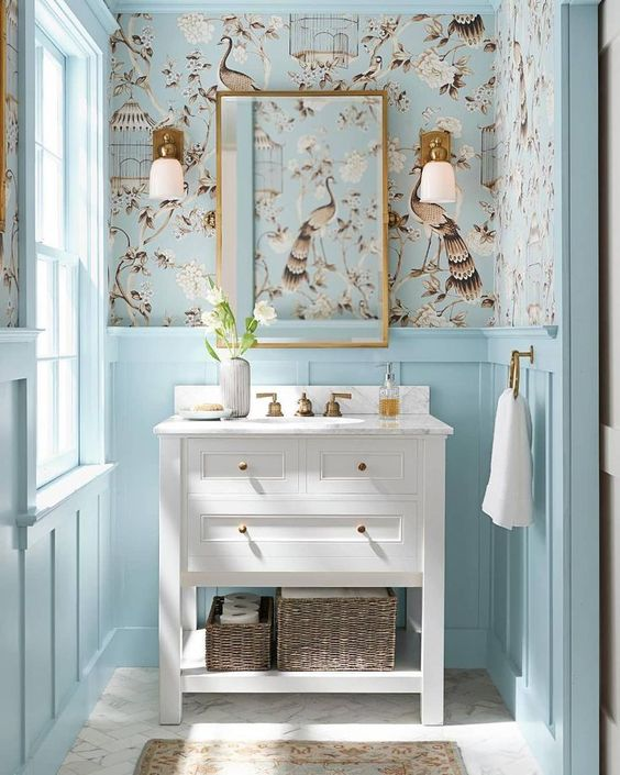 a light blue powder room done with pretty printed wallpaper and a rustic white vanity
