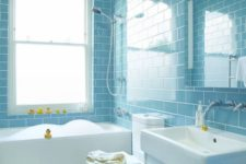 a light blue subway tile clad bathroom with white fixtures and appliances, yellow ducks for fun