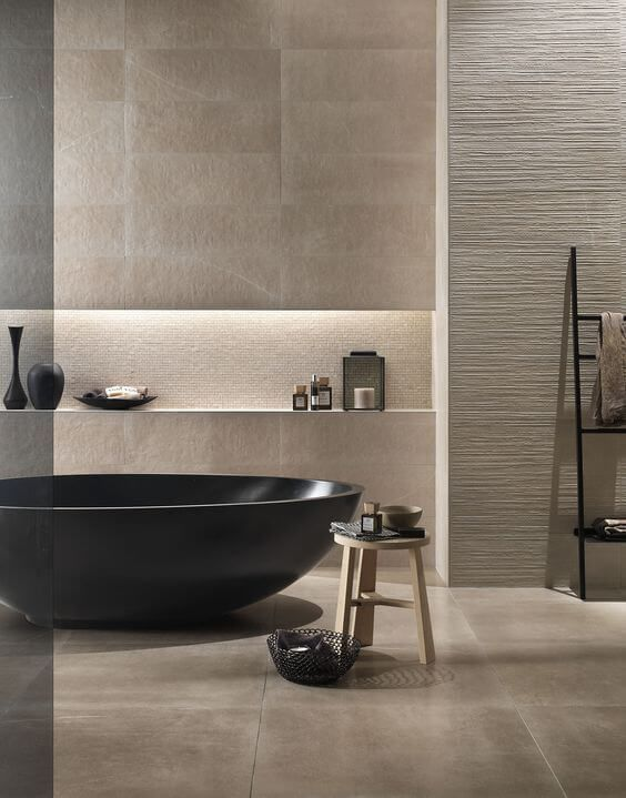 a luxurious beige bathroom with tiles and textural wall panels, a dakr bathtub and lots of bowls and cups