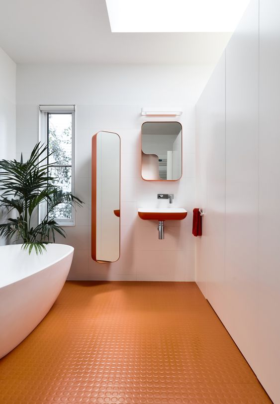 a minimalist bathroom with an orange penny tile floor and orange edges is a bold and chic idea