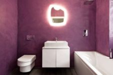 a minimalist bathroom with purple walls, a wooden floor and white appliances and a catchy shaped mirror