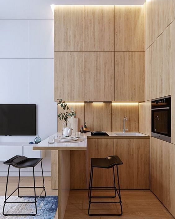 a minimalist kitchen with sleek plywood cabinets, a countertop for eating and cooking and leather stools