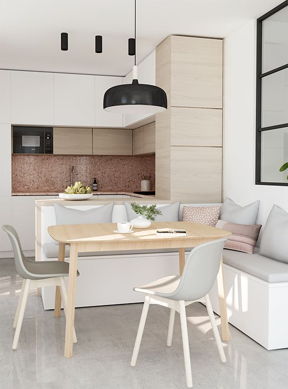 a minimalist kitchen with white and light-stained wooden cabinets with no hardware, a pendant lamp, a kitchen island with a built-in bench