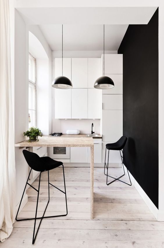 a minimalist monochromatic kitchen with white sleek cabinets, blakc pendant lamps, a plywood countertop, black stools and a black statement wall