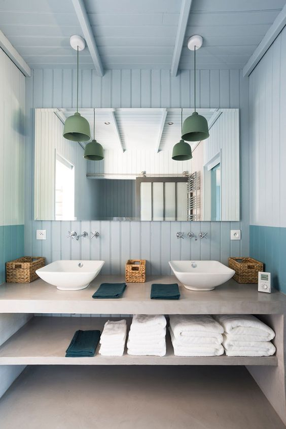 a modern light blue bathroom with beadboard, a concrete vanity and green pendant lamps over the sinks
