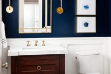 a navy statement wall and white paneling create a very elegant look and a vintage vanity adds to it