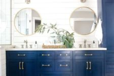a navy vanity and storage piece, gilded touches and a woven basket plus round mirrors