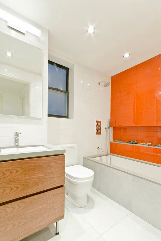a neutral contemporary bathroom with white tiles, concrete and wood and a statement orange tile wall