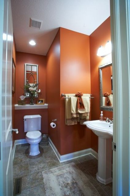 a powder room with rust colored walls, white appliances and a grey floor is a bright and chic idea