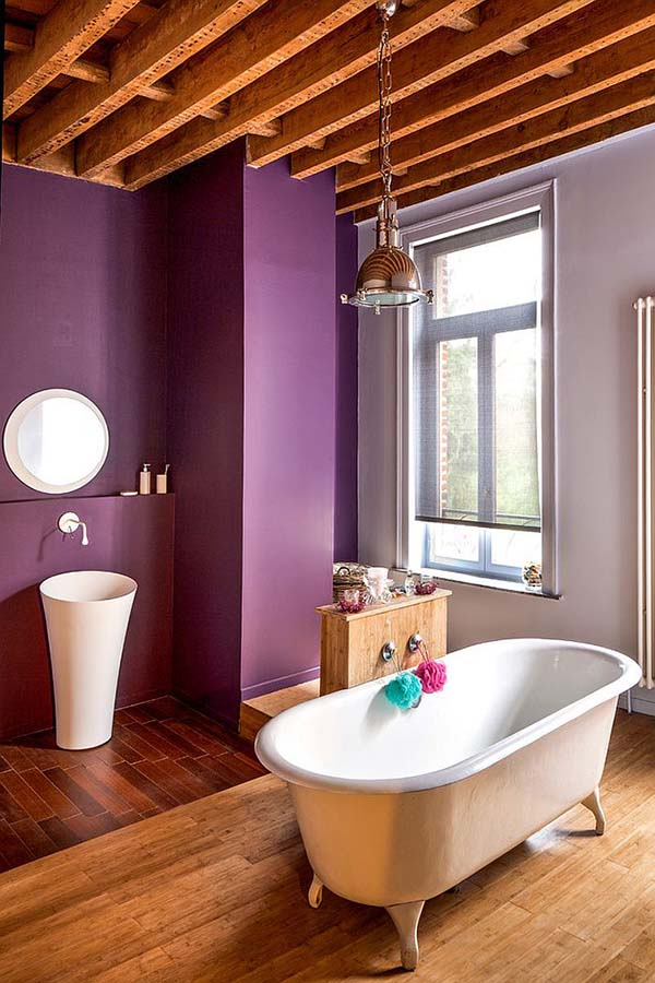 a purple farmhouse bathroom with a wooden ceiling with beams, a pendant lamp, a free standing sink and a vintage bathtub